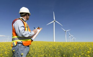 image of a wind farm and an inspection man wearing a hard hat and safety vest