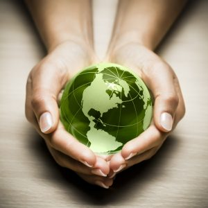 Photo of hands holding green globe